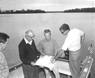 Walt Disney World - Roy O. Disney inspecting design plans on-site in Florida.