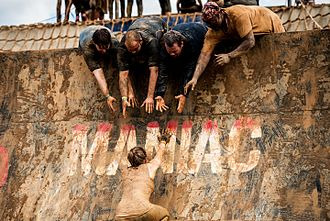 Obstacle racing - Rugged Maniac 2015. Four men offer a helping hand up the Warped Wall in Rugged Maniac.