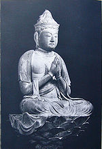 Three-quarter view of a cross-legged seated deity on a pedestal with hands joined as in prayer in front of the body.