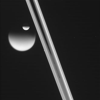 Transit (astronomy) - Dione transits Titan, as seen by the Cassini probe; in the background, little Prometheus is occulted by the rings of Saturn