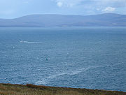 The attack site today, seen from a cliff above the bay. A small green wreck buoy is a few hundred metres away. A thin slick of oil is on the surface of the sea.