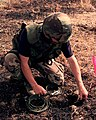Senior Airman Timothy Stimpson, U.S.A.F., prepares an unexploded BLU-97 bomblet for demolition in a field outside of Urosevac, Kosovo, on Aug. 10, 1999.jpg