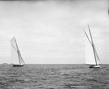 Black and white photograph of two yachts racing under full sail