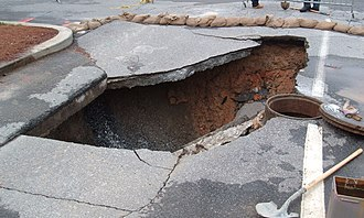Sinkhole - Collapse formed by rainwater leaking through pavement and carrying soil into a ruptured sewer pipe.