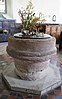 A circular sandstone font standing on an octagonal base, bearing a floral decoration