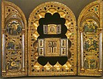 A golden, bejewelled triptych. The left and right wings each show three inlaid circular images; the centre panel has a scalloped surround housing two older triptychs, each containing a wooden Cross and showing Byzantine-style Greek lettering.