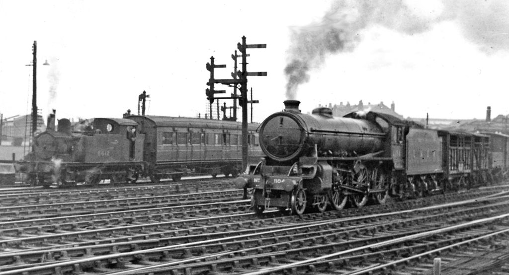 Stratford: typical scene with a Goods and an empty stock train. View westward, from the main Up platform: ex-GE major junction. Thompson B1 4-6-0 No. 1104 (built 12/46, withdrawn 4/64) is perhaps demeaned by being put on an Up local goods working from Temple Mills. Behind, one of the numerous ex-GE Holden 0-6-0Ts, LNE No. 8612 (formerly 7165) (built as GE No. 165 in 7/1901, withdrawn as BR No. 68612 in 6/61) continues the almost endless work of shunting carriages. The movements at this spot were continuous and meanwhile there was constant activity on the Low Level line just underneath.