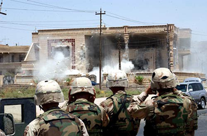 Qusay Hussein - U.S. Army soldiers from the 101st Airborne Division watch as a TOW missile strikes the side of a house of Uday and Qusay Hussein in Mosul, Iraq, 22 July 2003