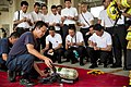 Tetsuo Kitaura, foreground, assigned to Commander, Navy Region Japan, demonstrates the differences between a U.S. and Japanese self-contained breathing apparatus to students of the Kumamoto Fire Academy 130823-N-ER662-088.jpg