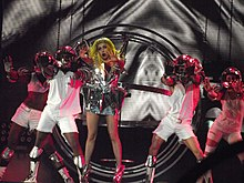 A blond woman in white pants and black bustier stands inside a number of metallic circular rings. She holds a microphone to her mouth with her left hand and her right hand makes a claw like gesture, the woman is flanked by men and women in white dress and fierce expressions with their eyes being white in color.