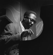 Black and white photograph of a man playing piano