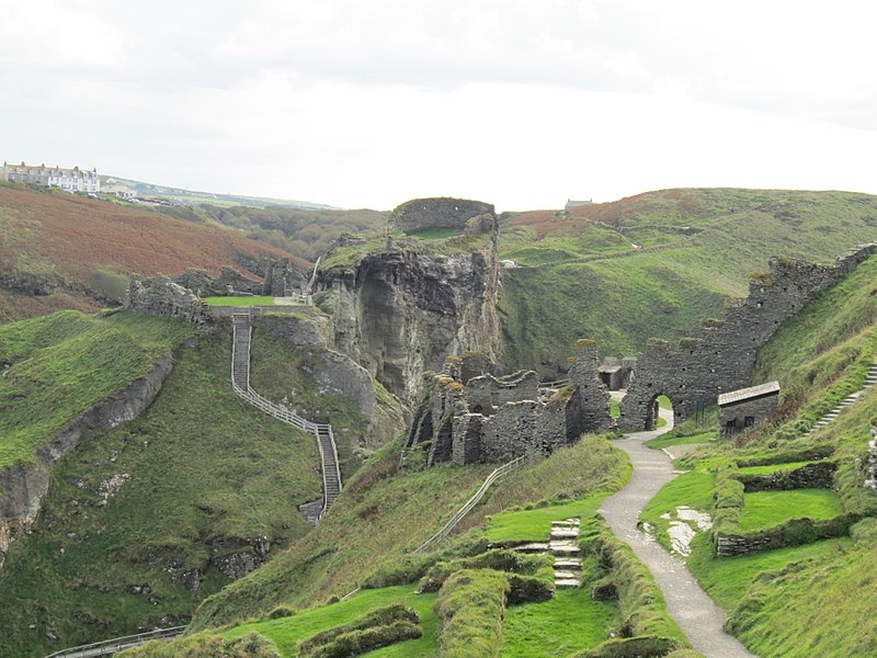 Tintagel Castle in Cornwall, England. The castle's ruined walls rise above steep grassy slopes and rocky cliffs. (Photo by Robert Lindsell. Used under CC BY 2.0 license.)