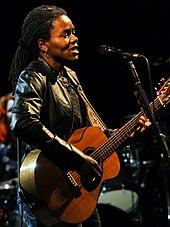 Une femme avec des dreadlocks debout derrière un pied de micro.  Elle porte une veste en cuir et joue de la guitare.