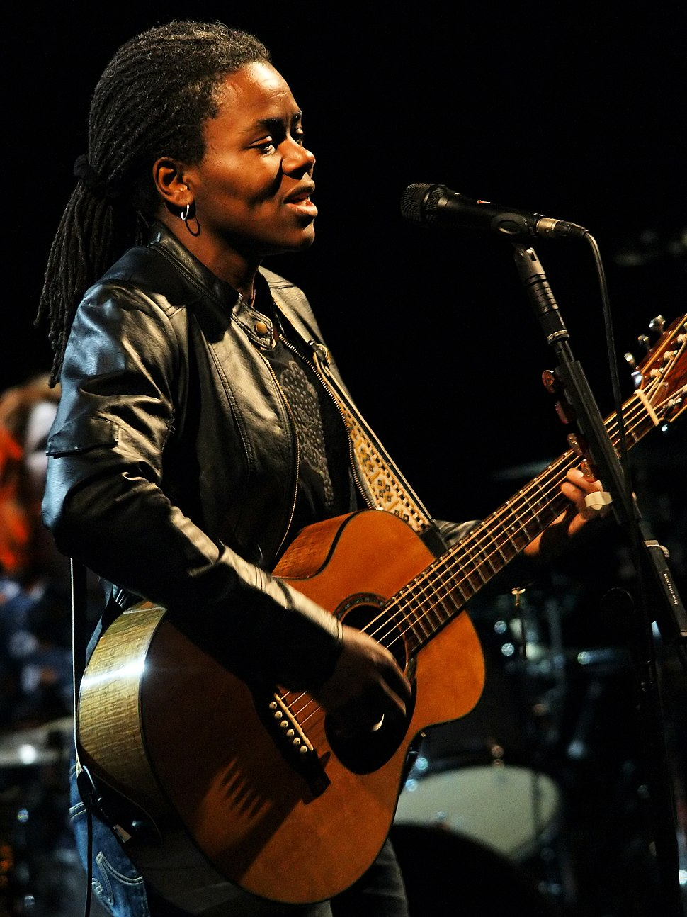 A woman with dreadlocks standing behind a microphone stand. She is wearing a leather jacket and playing a guitar.