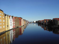 View of Nidelva, seen downstream from the Old Town Bridge. Some storehouses shown to the left had cranes, for hoisting goods from boats below.
