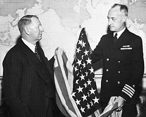U.S. Secretary of the Navy Frank Knox receives the first U.S. flag had been raised over Kwajalein, 29 February 1944 (80-G-44879)