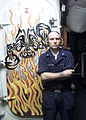 US Navy 030402-N-5027S-005 Machinist's Mate 3rd Class Jamie Eichenlaub of Williamsport, Penn., poses in front of a mural he has painted on a quick acting watertight door.jpg