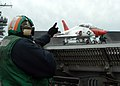 US Navy 050309-N-8704K-001 Aviation Boatswain's Mate 1st Class Robert McCray signals that the number one catapult is ready to launch a T-45A Goshawk.jpg