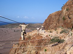 US Navy 070128-A-0000X-001 Explosive Ordinance Disposal 2nd Class Chris Vann and Information Systems Technician 2nd Class Brian Bell, cross a three-rope bridge during a French Foreign Legion Commando Course in Arta, Djibouti.jpg