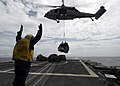 US Navy 080718-N-4236E-491 Boatswain's Mate 3rd Class Francisco Vega guides an MH-60S Seahawk from Helicopter Sea Combat Squadron 28 (HSC-28) bringing mail, supplies, and food aboard the guided-missile cruiser USS Vella Gulf (C.jpg