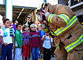 US Navy 081007-N-4044H-251 Firefighter Elio Dentoni shows Naples Elementary School students the protective firefighter suit and the proper way to put it on.jpg