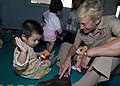 US Navy 090714-N-6770T-143 Rear Adm. Nora Tyson, commander, Logistics Group Western Pacific, plays with a child at the Pattaya Orphanage.jpg