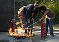 US Navy 091005-N-9860Y-001 Alan Sprouse, a Navy Region Northwest Fire and Emergency Services fire inspector, helps a School Age Care Programs student extinguish a grease fire.jpg