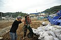 US Navy 110714-N-KK192-128 Construction Electrician 1st Class Joshua Thonissen and a Japanese volunteer load bags of mud into the scoop of a front.jpg
