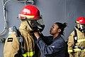 US Navy 110729-N-WV964-024 Damage Controlman Fireman Jasmine Bly checks a Sailor's firefighting ensemble during basic damage control training aboar.jpg