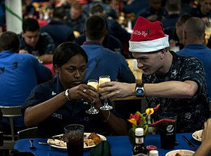 US Navy 111225-N-DR144-033 Machinist's Mate 3rd Class Nazierah Dowell and Electronics Technician 3rd Class Bryan McGee toast over Christmas dinner.jpg