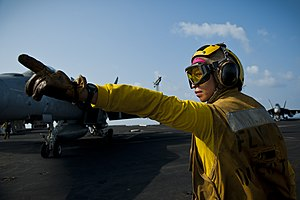 US Navy 120109-N-BT887-025 Aviation Boatswain's Mate (Handling) 3rd Class Adelita Sisporon directs an F-A-18E Super Hornet from the Tophatters of S.jpg