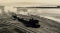 Vista de una locomotora de carga, pasando por la orilla del mar, ca. 1913 (cropped).png