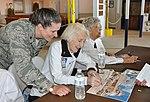 WASP Mary Vendeventer smiles as she signs autographs on museum memorabilia inside the Avenger Field hangar.JPG