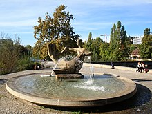 Circular fountain surrounded by pavement. The fountain's center is a sculpture of a pair of abstract human figures.