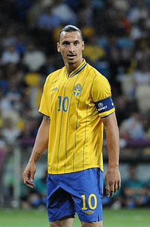 A photograph of a man with dark hair wearing a yellow football shirt, blue shorts and a dark blue captain's armband on his arm, the man is looking away from the camera.