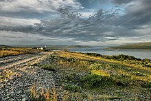 A picture of Rybachy Peninsula on a partly cloudy July day. The Soviet Union demanded that Finland cede the peninsula, its northernmost point at the time, along with other areas. The sun is either rising or setting and shines on the long grass at an angle. A body of water, the Barents Sea, fills a quarter of the picture. A gravel road leads to a lone house in the distance.
