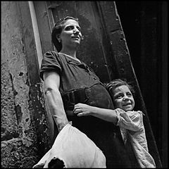 """Children In Naples, Italy"". Little girl holding her pregnant mother. Photographed by Lieutenant Wayne Miller, July 1944. U.S. Navy Photograph, now in the collections of the National Archives.jpg"