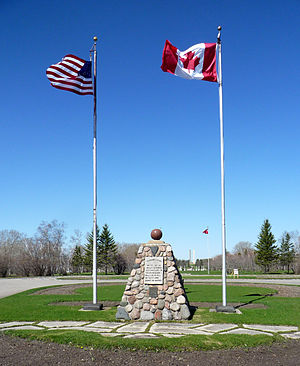 "International Peace Garden - The original monument, erected in 1932 and addressed ""To God in His Glory"", at the front of the park: the border runs through the ball, and continues to between the Peace Tower, seen in the background. The Manitoba flag is seen to the right, behind the Canadian flag."