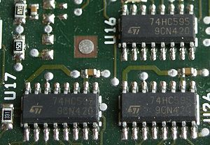 7400 series - Surface-mount 74HC595 shift registers on a PCB. This 74HC variant of the 74595 uses CMOS signalling voltage levels while the 74HCT595 variant uses TTL signalling levels.