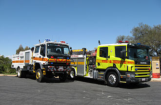 """Australian Capital Territory Rural Fire Service - An ACT Rural Fire Service CAFS Isuzu tanker (white) and an ACT Fire Brigade Scania 94D 260 truck (yellow) pumper. Both with """"FIRE"""" in mirror writing (""""ERIF"""")."""
