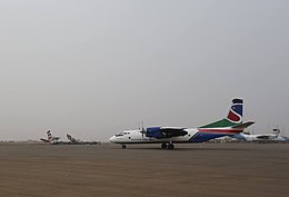 A colourful twin-engine aircraft taxiing on a dusty airport apron under a grey sky
