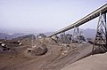 ASC Leiden - F. van der Kraaij Collection - 13 - 007 - LAMCO J.V. A flat belt conveyor on a tall iron construction in a landscape with open pit mining for iron ore - Yekepa, Nimba county, Liberia - 1976.jpg