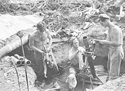 Soldiers in a gun pit with a mortar tube