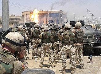 Uday Hussein - Soldiers of the 101st Airborne Division and U.S. Special Operations (Task Force 20) watch as a TOW missile strikes the side of a house occupied by Uday and Qusay Hussein in Mosul, on 22 July 2003