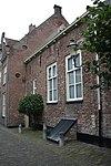 foto van Laag, eenvoudig woonhuis, aan singelzijde gepleisterd. Rechte lijst. Het oude muurwerk van de stadsmuur duidelijk zichtbaar. Vormt een geheel met nr 11