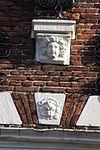 foto van Huis met trapgevel, met mozaiekwerk, sierankers en maskers, bekroond door schilddragende leeuw. Achterzijde eenvoudige topgevel van vroeger datum