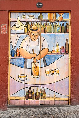 """One of the doors of the """"ArT of opEN doors"""" project, showing the preparation of Poncha, a traditional drink of Madeira, with a """"caralhinho"""", a kind of a beater"""