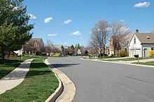 A meandering suburban street. On both sides there are rows of houses with lawns in front of them.