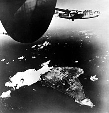 A four engined World War II-era aircraft flying above an island which is party covered in cloud as well as smoke. Sections of two other aircraft are visible.