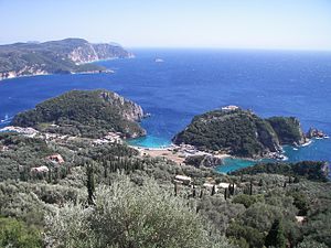 The bay of Palaiokastritsa in Corfu as seen from Bella vista of Lakones. Corfu is considered to be the mythical island of the Phaeacians. The bay of Palaiokastritsa is considered to be the place where Odysseus disembarked and met Nausicaa for the first time. The rock in the sea visible near the horizon at the top centre-left of the picture is considered by the locals to be the mythical petrified ship of Odysseus. The side of the rock toward the mainland is curved in such a way as to resemble the extended sail of a trireme